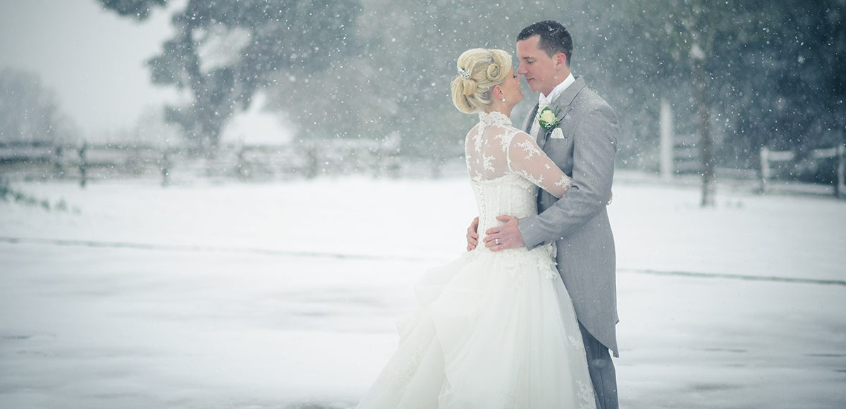 Newlyweds share a kiss as the snow falls on their winter wedding day at Gaynes Park in Essex
