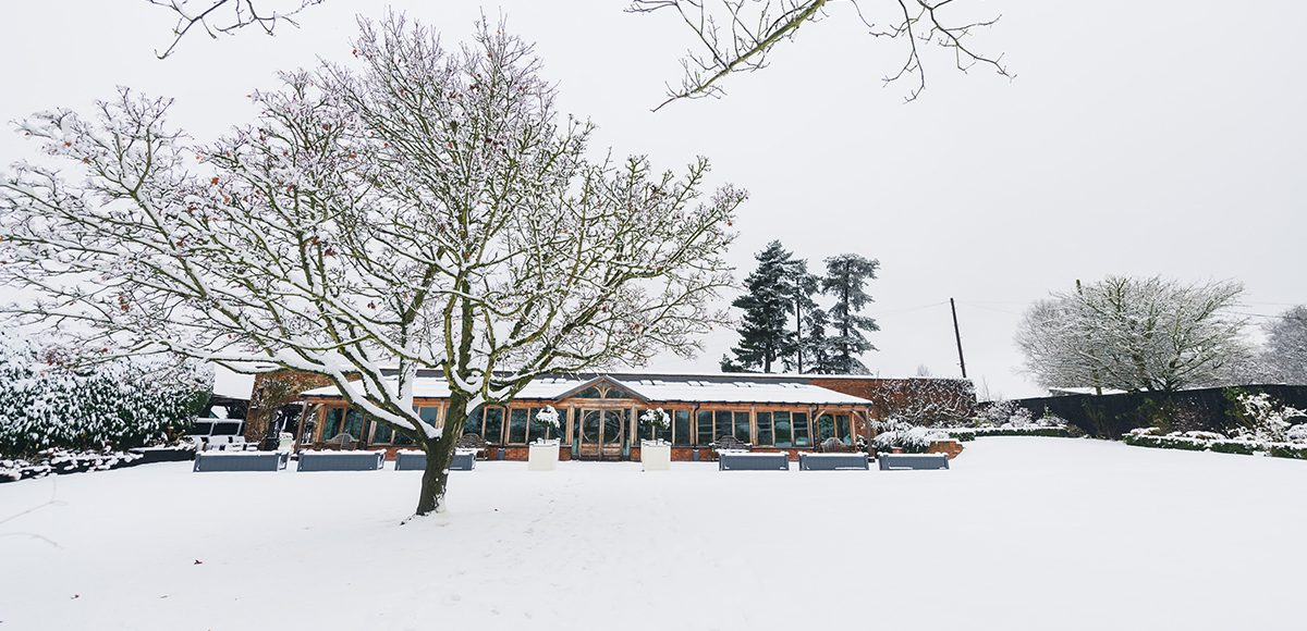 The Orangery at Gaynes Park wedding venue in Essex is covered in snow during a winter wedding