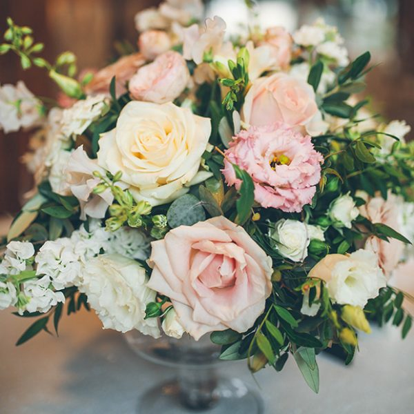 Pink and cream roses look elegant within the table centrepieces in the Mill Barn at Gaynes Park
