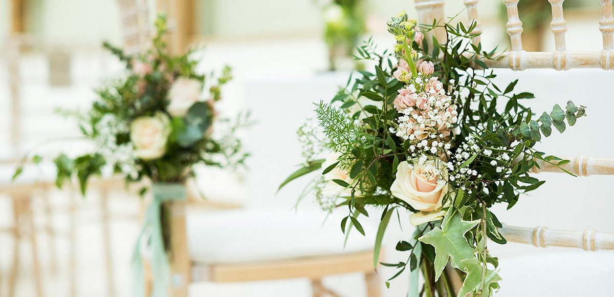Flowers tied to pew ends help to create a rustic wedding ceremony setting at Gaynes Park