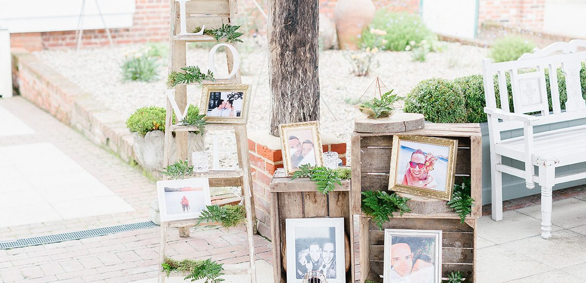 At Gaynes Park wooden crates are decorated with photos and flowers for a rustic wedding focal point