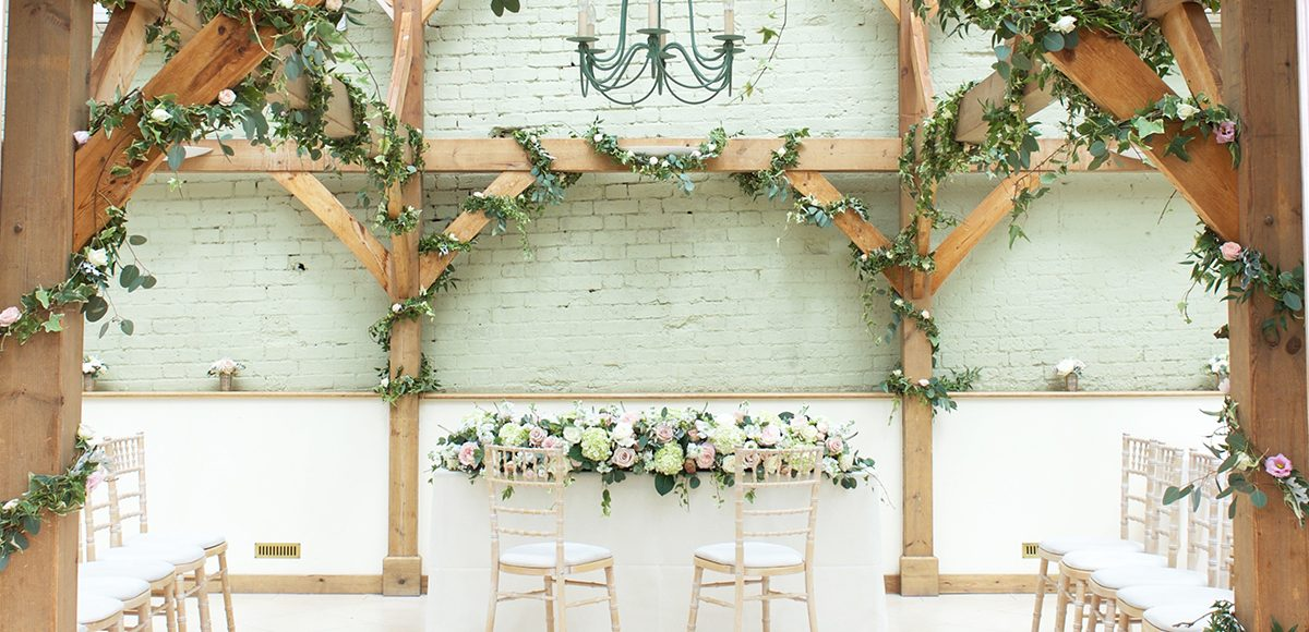 The beams in the Orangery at Gaynes Park are decorated with wedding flowers for a rustic wedding