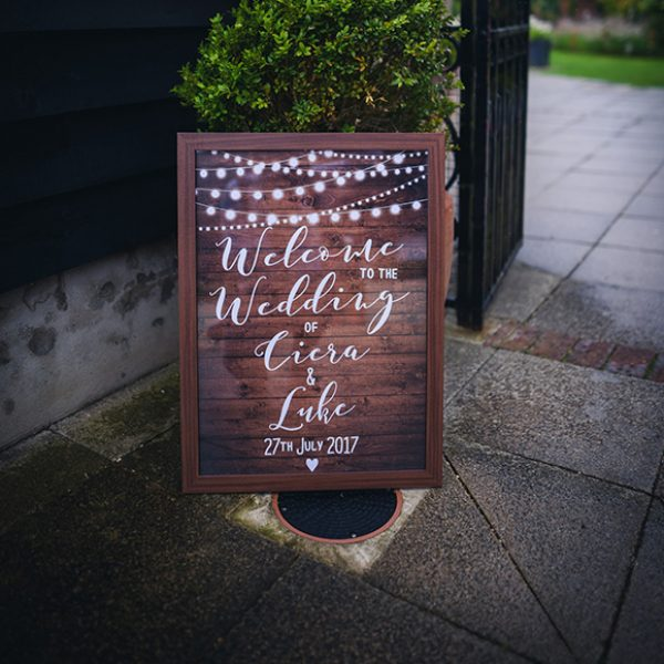 A wooden wedding sign welcomes guests to a rustic wedding at Gaynes Park