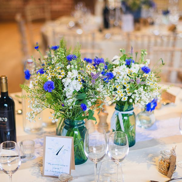 At Gaynes Park wild flowers in jam jars are used as rustic wedding table centrepieces