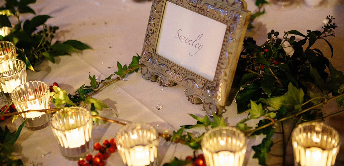 Lots of tea-lights add romance in the Mill Barn at Gaynes Park for a beautiful winter wedding