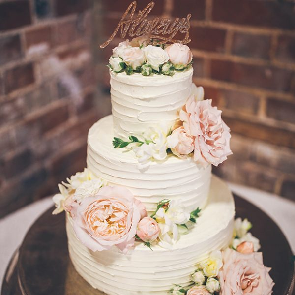 At Gaynes Park a three-tiered white wedding cake was decorated with pink flowers and a Harry Potter cake topper