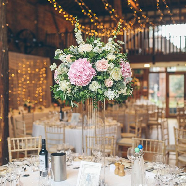 For their summer wedding the couple chose pink wedding flowers to dress their tables in the Mill Barn at Gaynes Park