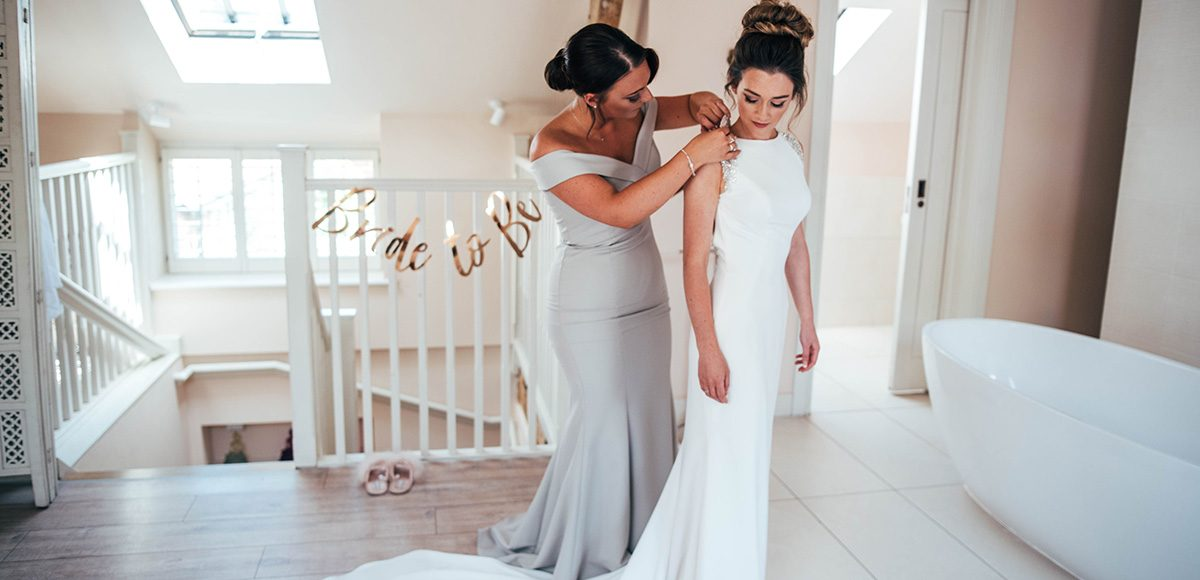 A bridesmaid helps the bride with finishing touches to her wedding dress in Apple Tree Cottage at Gaynes Park