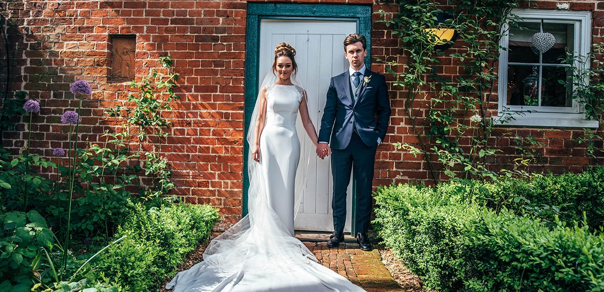 The bride and groom stand in front of Apple Tree Cottage at Gaynes Park for some wedding photographs