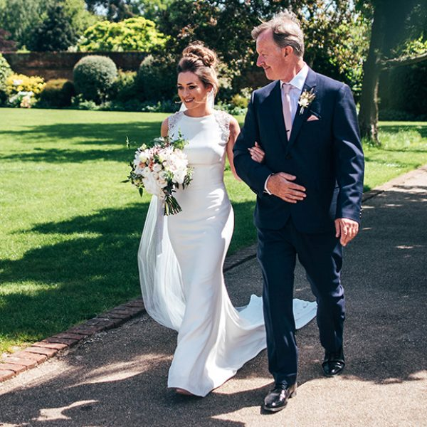 The bride and her father walk down the wedding aisle in the Walled Garden at Gaynes Park