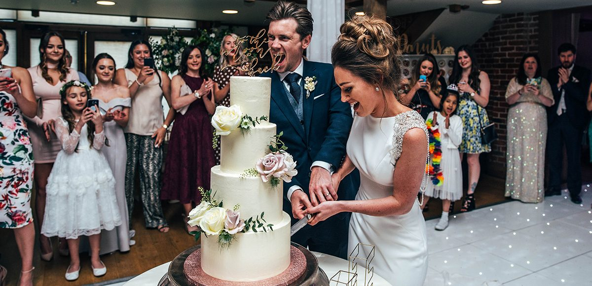 The newlyweds cut their wedding cake in front of guests in the Mill Barn at Gaynes Park