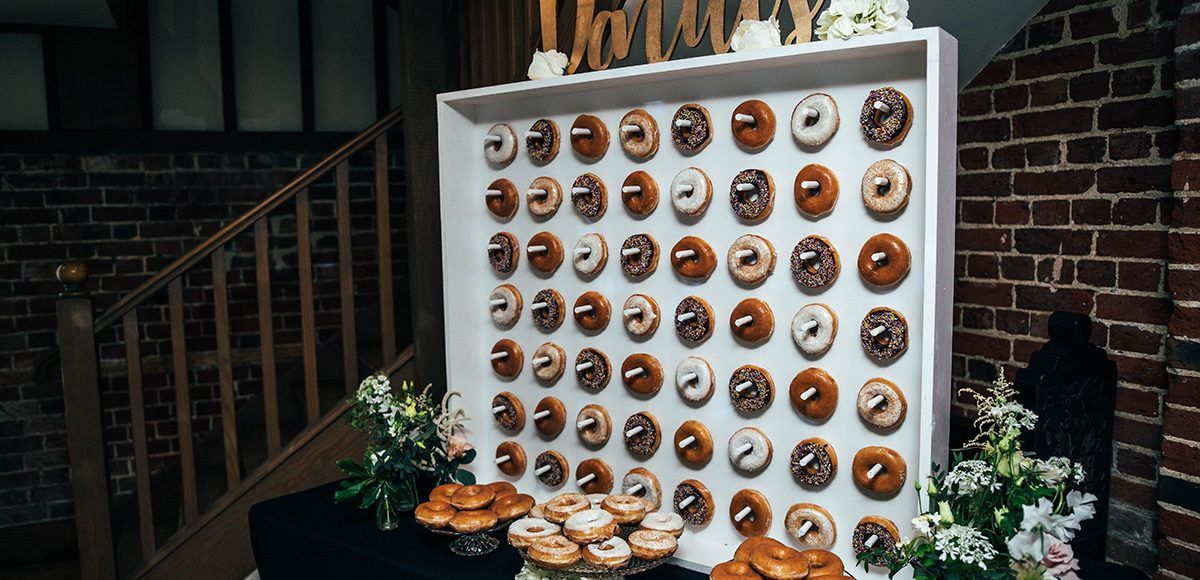 The couple chose to have a doughnut wall as a focal point during their wedding reception at Gaynes Park