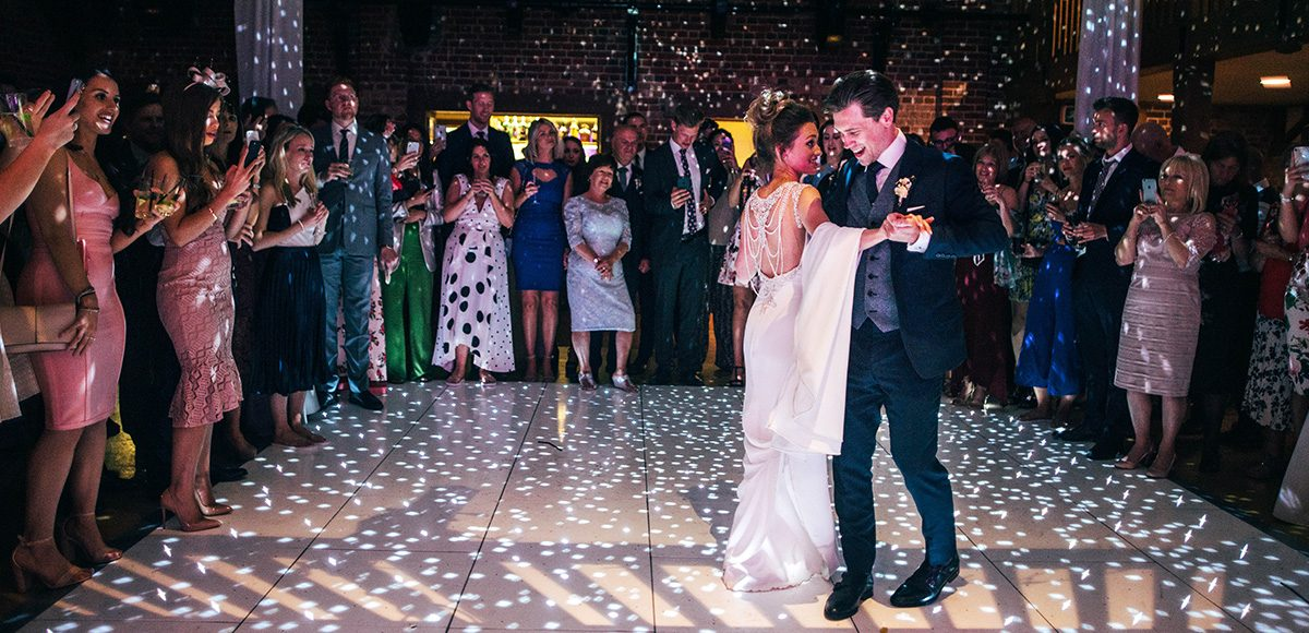 The newlyweds share their first dance during their wedding reception in the Mill Barn at Gaynes Park