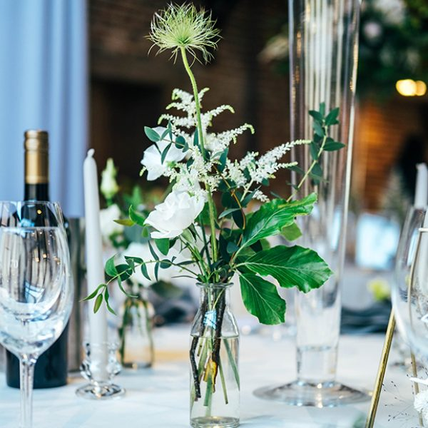 For a wedding reception milk bottles were filled with wild wedding flowers and placed on tables in the Mill Barn at Gaynes Park