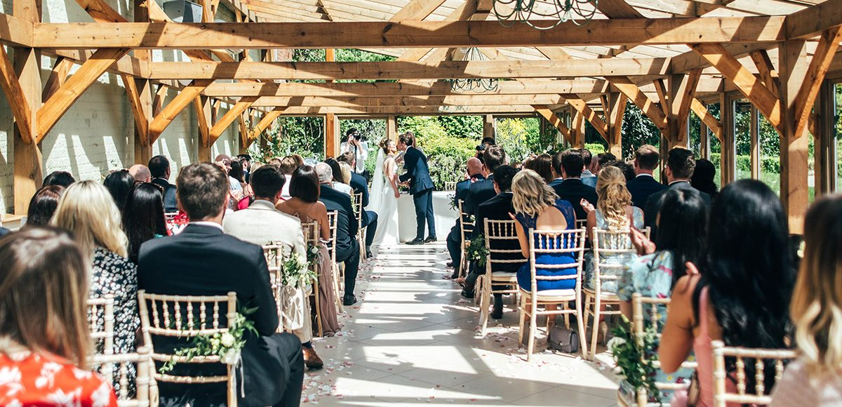 Newlyweds share their first kiss as husband and wife in the Orangery at Gaynes Park