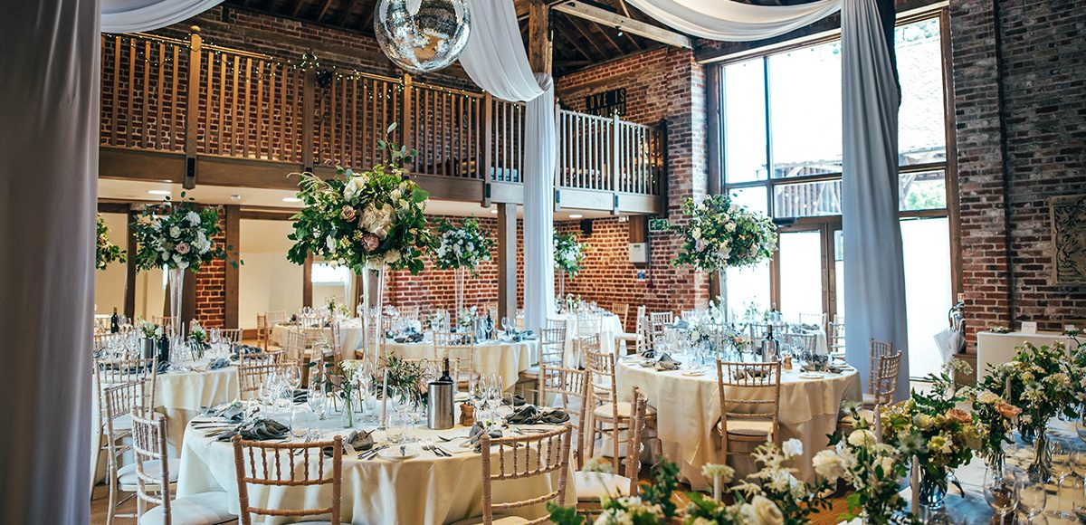 The Mill Barn at Gaynes Park is set up for a beautiful wedding reception