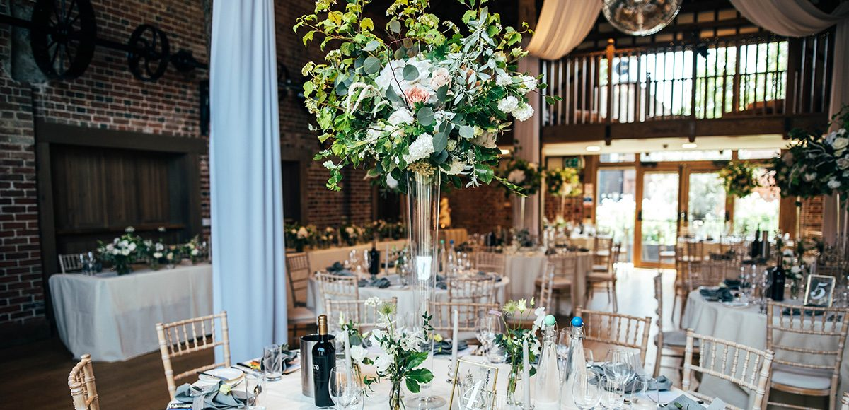 The Mill barn at Gaynes Park is decorated with florals for a beautiful wedding reception
