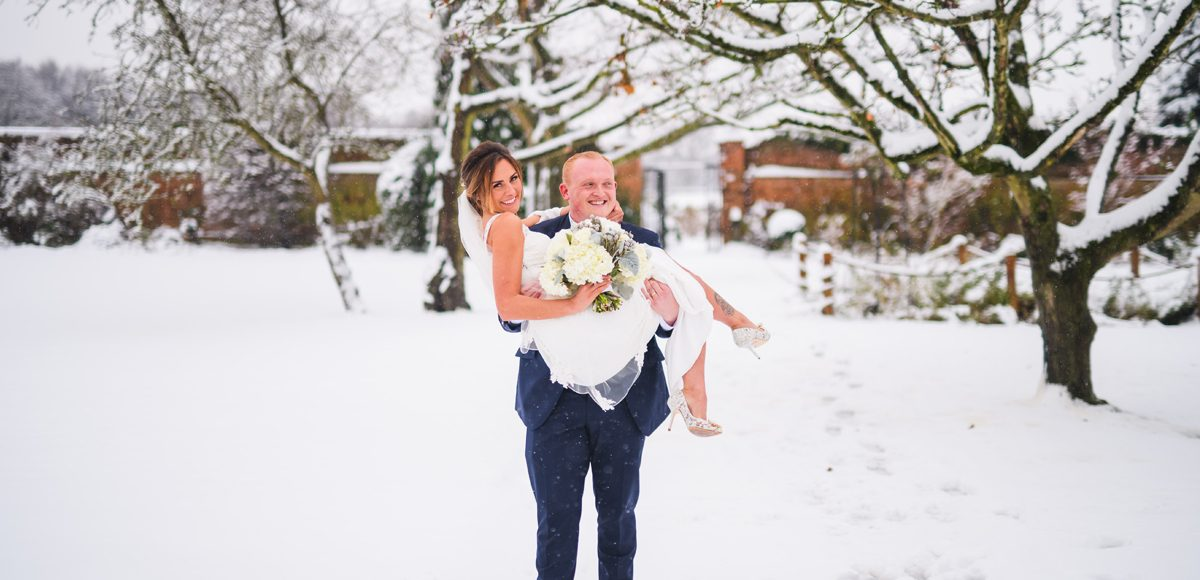 Newlyweds make the most of the snow for stunning photographs in the Walled Gardens at Gaynes Park