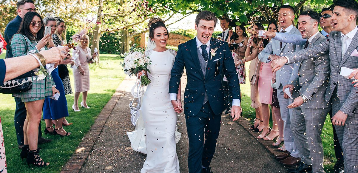 Newlyweds are showered in confetti following their wedding ceremony at Gaynes Park