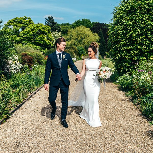 The newlyweds take a stroll down the Long Walk at Gaynes Park after their wedding ceremony