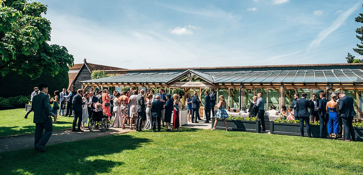 Wedding guests enjoy a drinks reception outside the Orangery at Gaynes Park