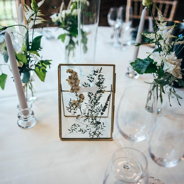 Frames filled with pressed flowers were used as unique table numbers for this beautiful wedding at Gaynes Park