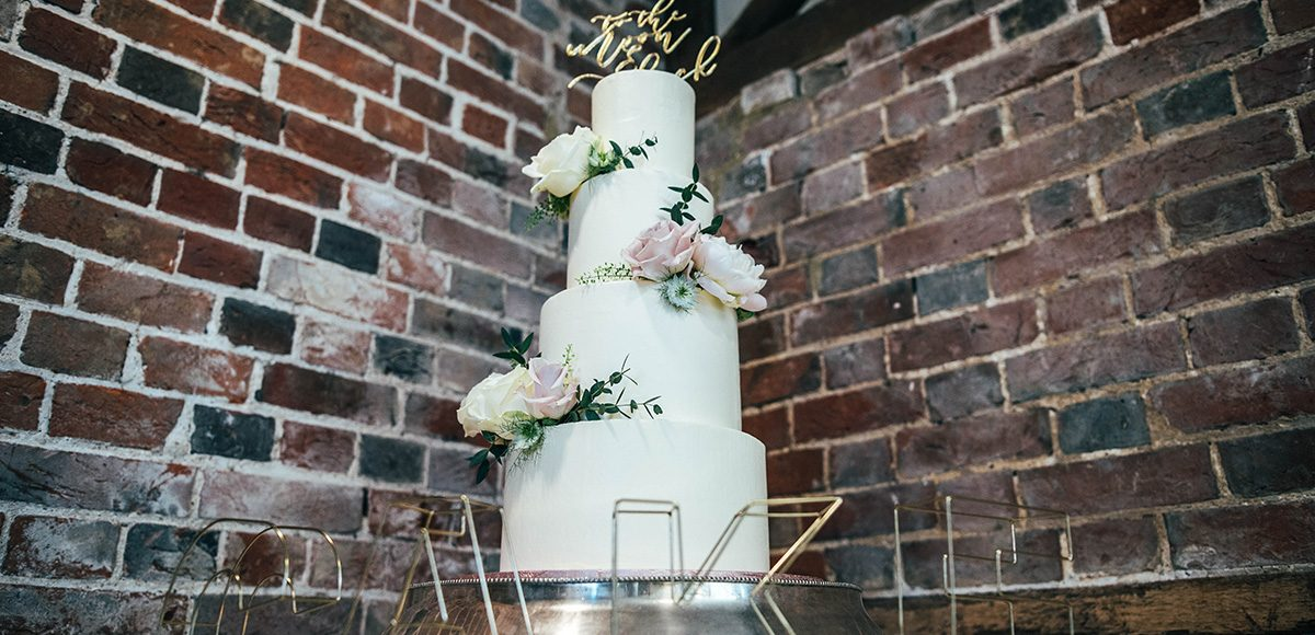 A white three tiered wedding cake was adorned with wedding flowers for this classic wedding at Gaynes Park
