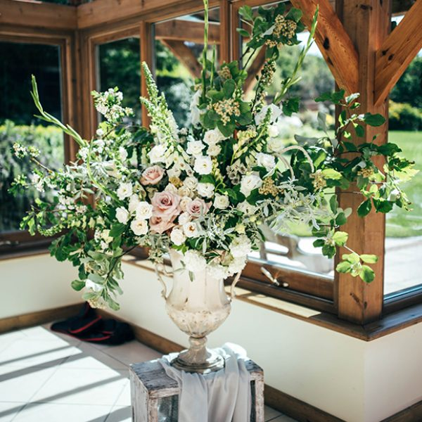 Large urns are filled with wedding flowers and placed in the Orangery at Gaynes Park