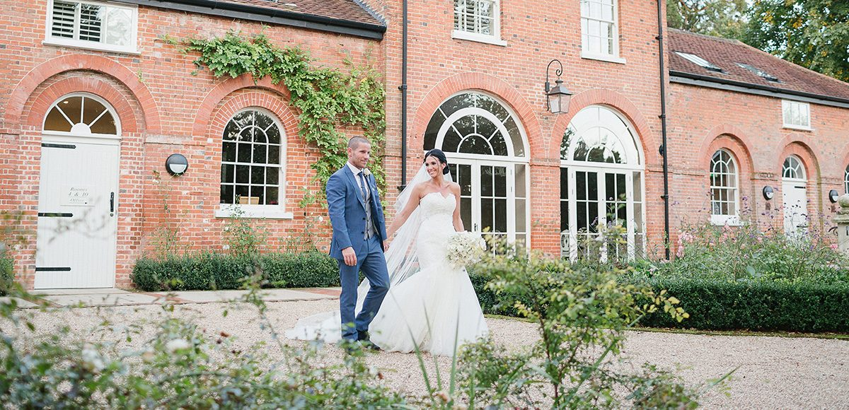 A bride and groom explore the glorious grounds at Gaynes Park wedding venue in Essex on their wedding day