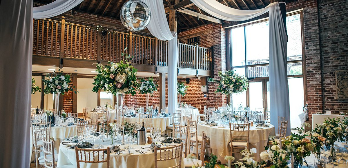 The Mill Barn at Gaynes Park wedding venue in Essex is set up for a beautiful wedding breakfast