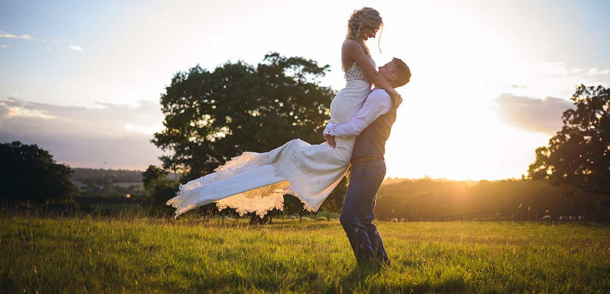 Newlyweds enjoy the countryside that surrounds Gaynes Park as the sun sets on their wedding day