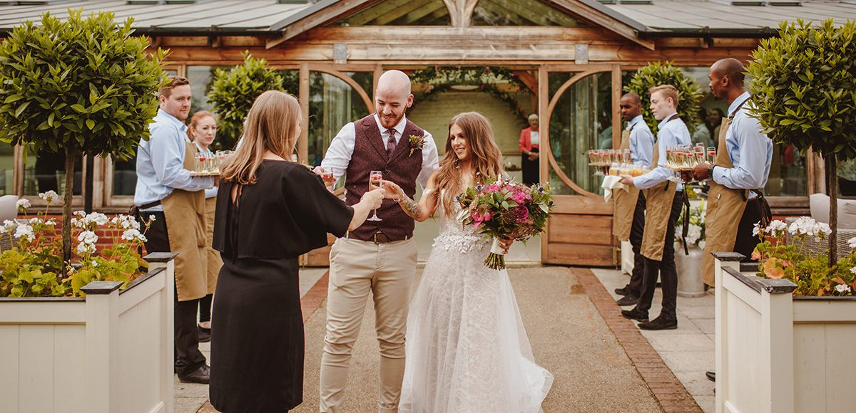 Newlyweds enjoy their drinks reception in the Walled Gardens at Gaynes Park wedding venue in Essex