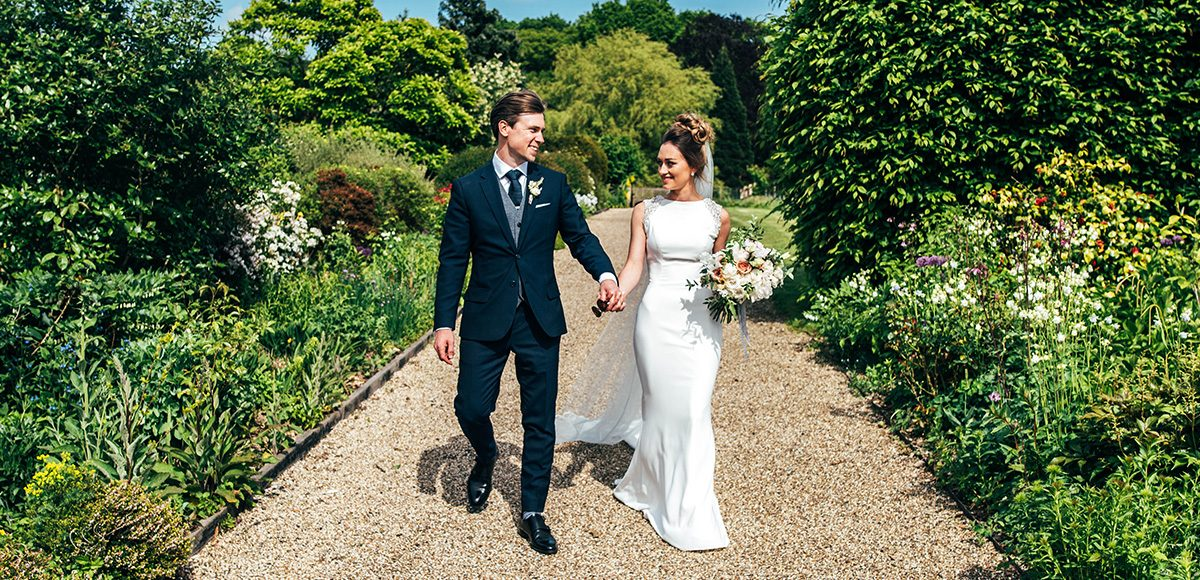 Newlyweds take a stroll down the Long Walk at Gaynes Park wedding venue in Essex