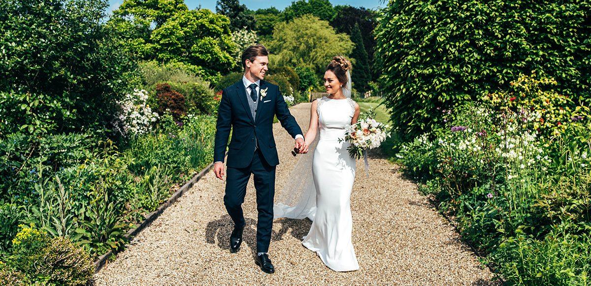 Newlyweds take a stroll down the Long Walk at Gaynes Park wedding venue in Essex