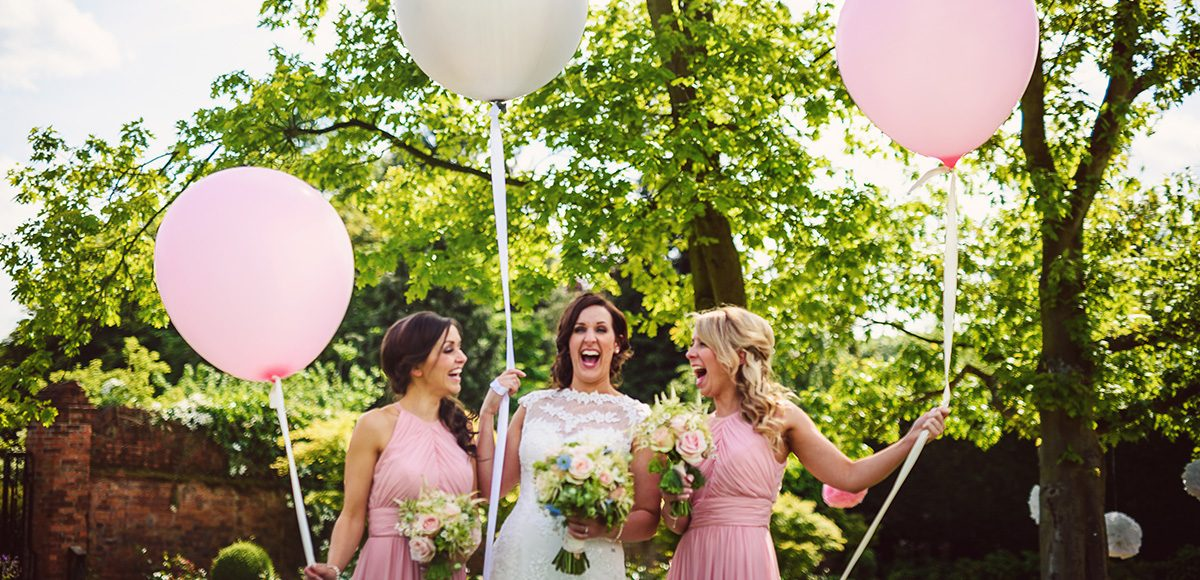 In the gardens at Gaynes Park a bride and her bridesmaids hold giant wedding balloons
