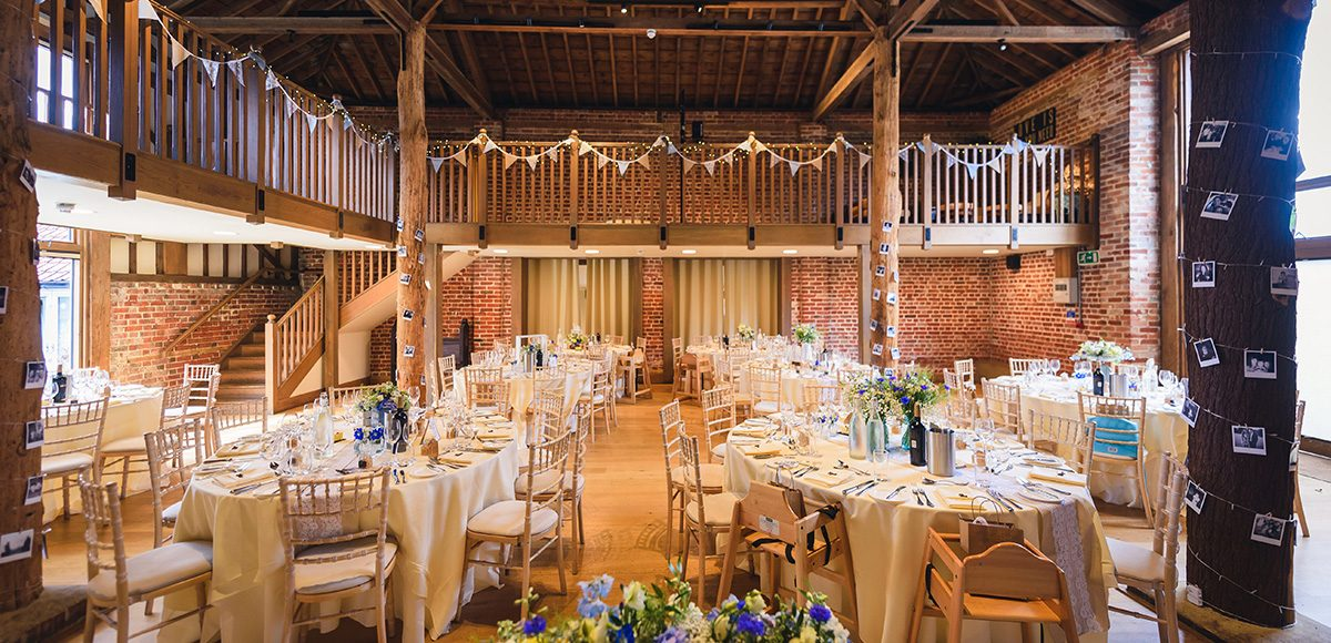 The Mill Barn at Gaynes Park is set up for a rustic wedding reception