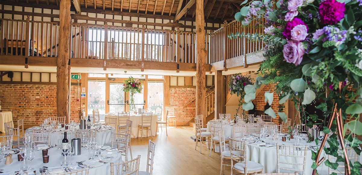 The Mill Barn at Gaynes Park wedding venue in Essex is dressed for a summer wedding reception