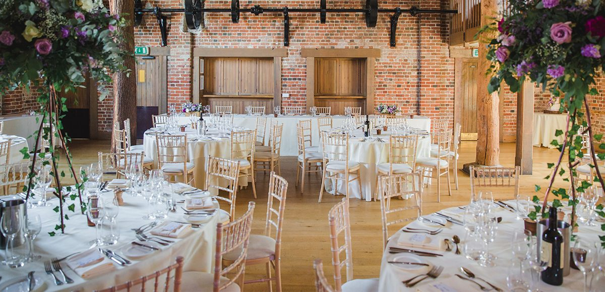 The Mill Barn at Gaynes Park in Essex is set up for a summer wedding reception