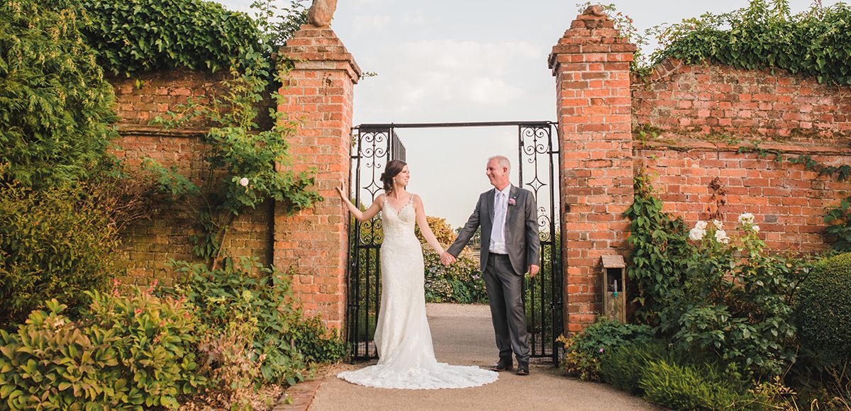 Newlyweds enjoy the walled gardens at Gaynes Park wedding venue in Essex on their wedding day
