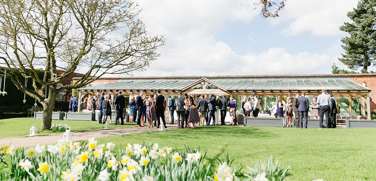 Guests enjoy a spring wedding drinks reception outside The Orangery at Gaynes Park