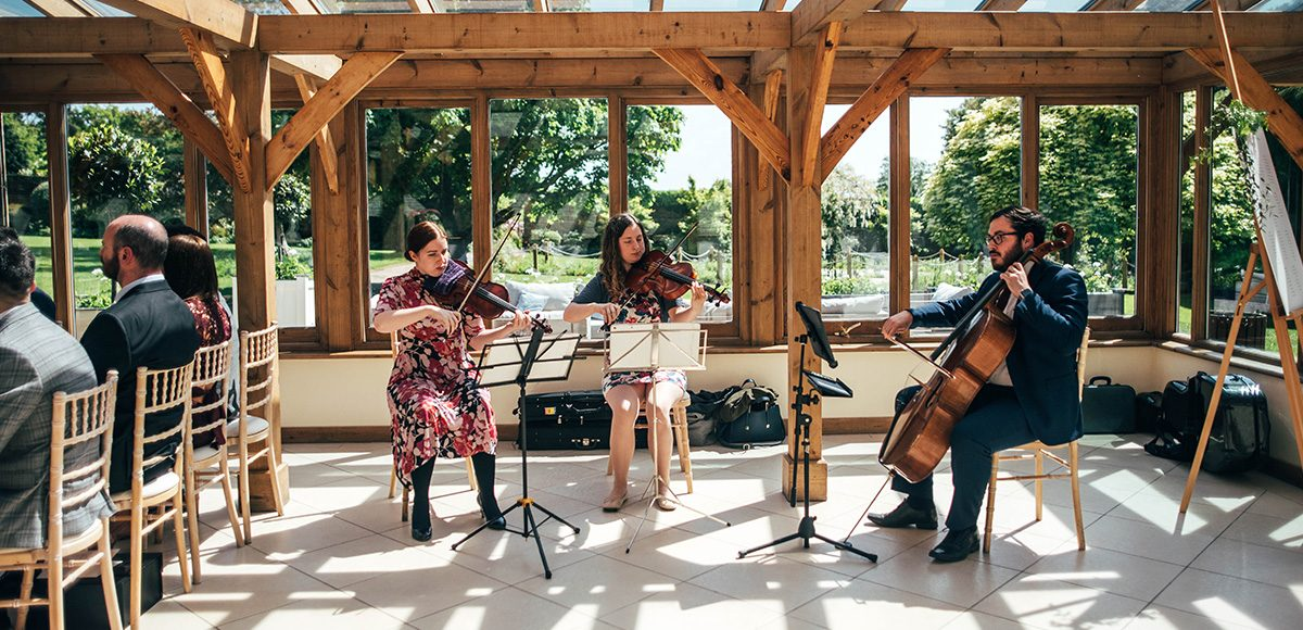 A string quartet plays in the Orangery at Gaynes Park during a wedding ceremony