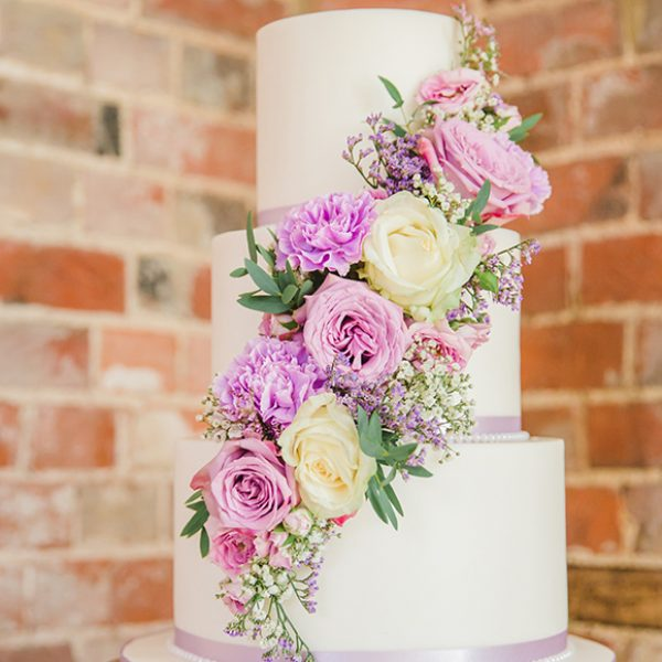 A traditional three-tiered white wedding cake is adorned with pink wedding flowers for a wedding at Gaynes Park