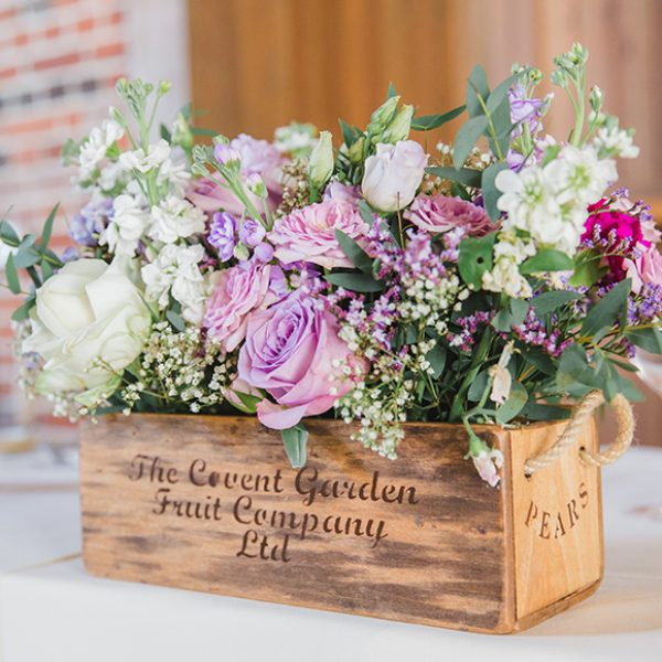 Wedding flowers sit in a rustic wooden crate for a summer wedding at Gaynes Park
