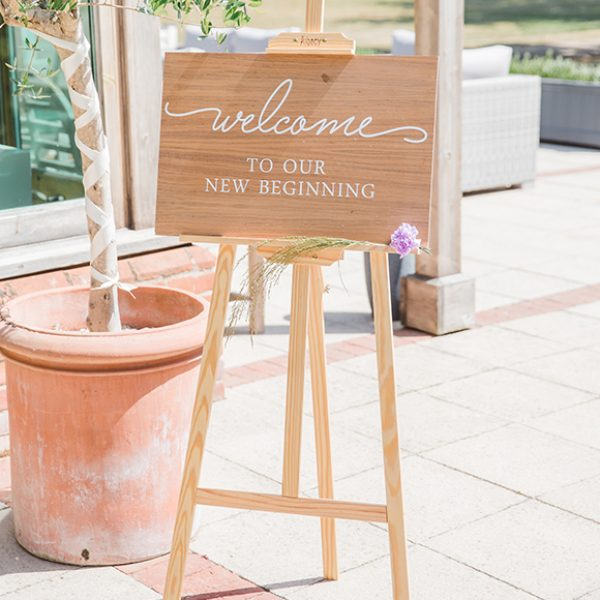 The couple welcome guests to their wedding at Gaynes Park with a rustic wedding welcome sign