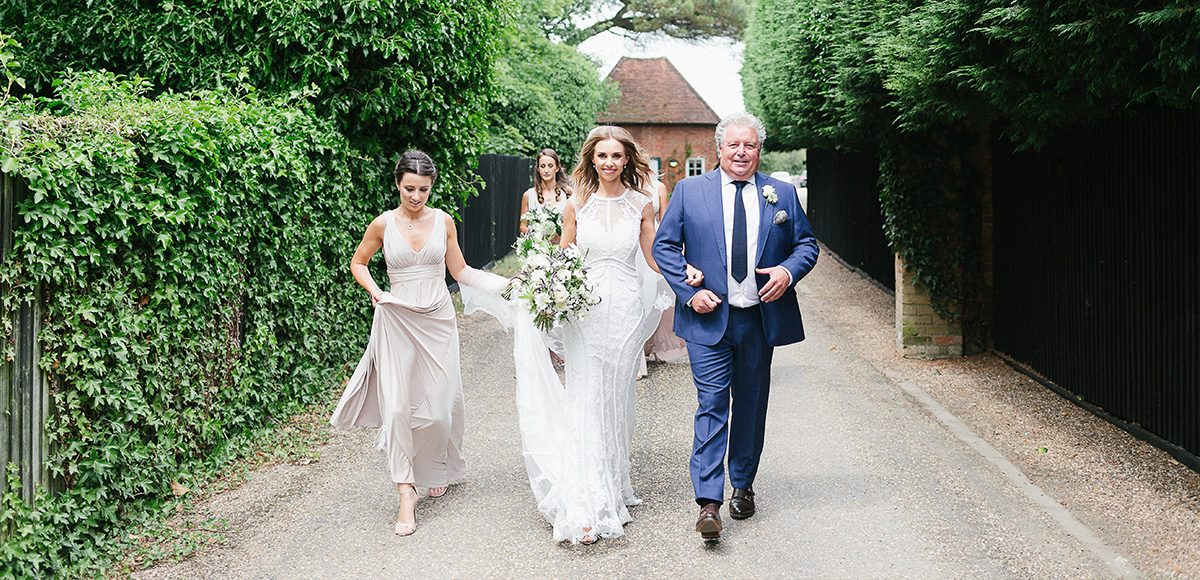 The bride and her bridal party make their way to the Long Walk at Gaynes Park before walking down the wedding aisle