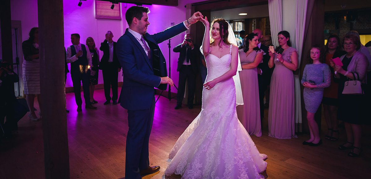 A bride and groom perform their first dance in front of guests in the Mill Barn at Gaynes Park in Essex