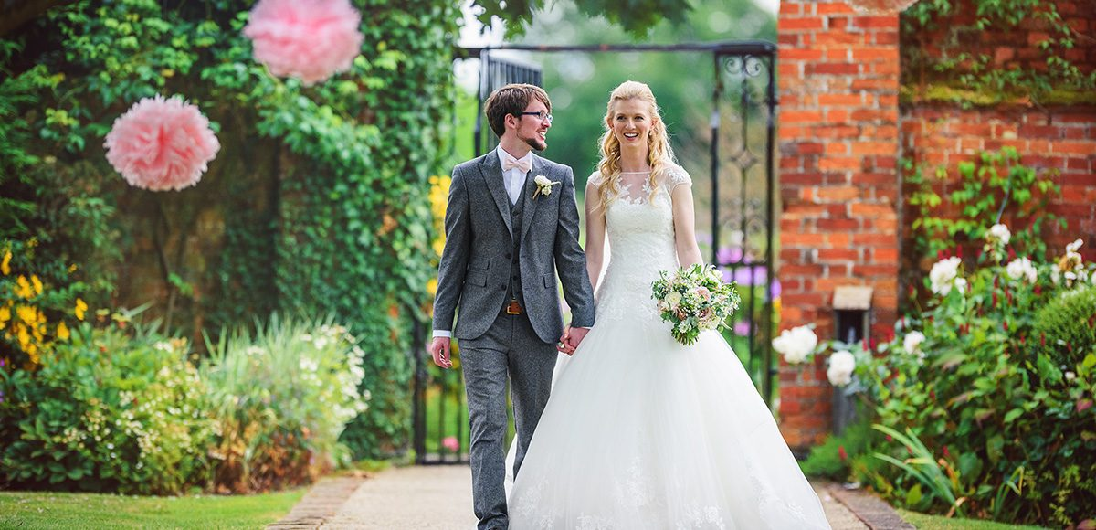 The bride and groom explore the beautiful walled gardens at Gaynes Park in Essex