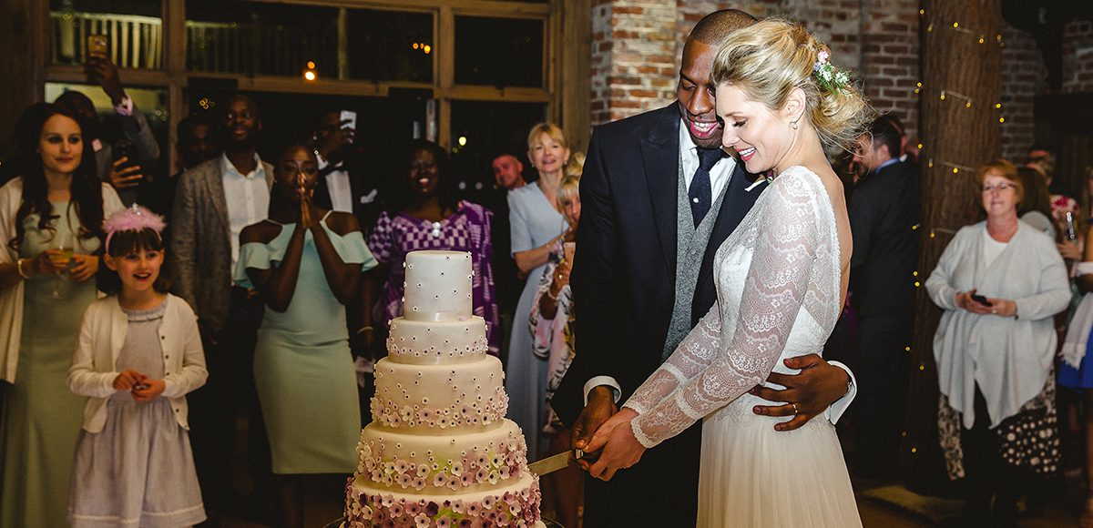 A bride and groom cut their wedding cake in front of guests in the Mill Barn at Gaynes Park in Essex