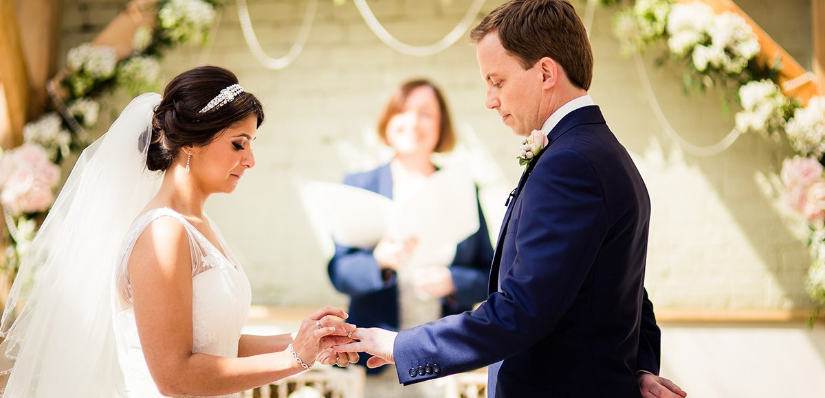 The bride and groom say their wedding vows in the Orangery at Gaynes Park in Essex