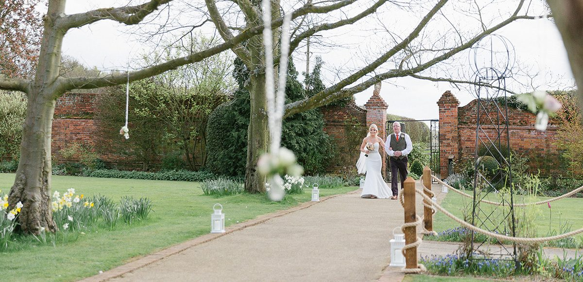 The bride and her father walk down the wedding aisle through the beautiful gardens at Gaynes Park